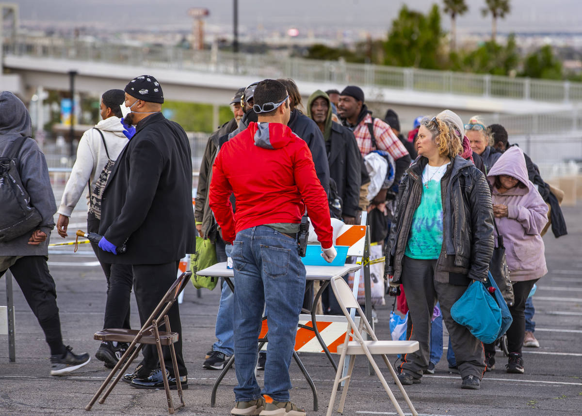 Homeless people line up the be screened as they enter the temporary shelter in the upper parkin ...