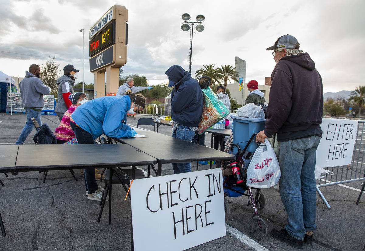 Homeless people enter and receive sheets and water at the temporary shelter in the upper parkin ...