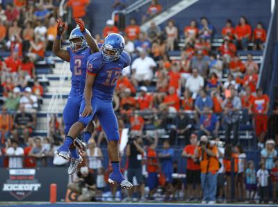 Quarterback Jarrett Solomon, right, of Bishop Gorman High School celebrates with teammate Ta ...