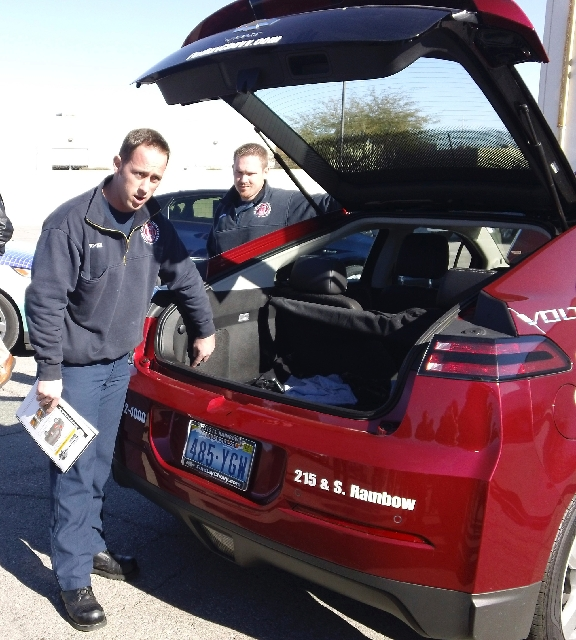 Firefighters Charles Howell and Michael Brennan teach the Traffic Incident Management coalition techniques for disconnecting a Chevrolet Volt's 12-volt auxiliary battery. Findlay Automo ...