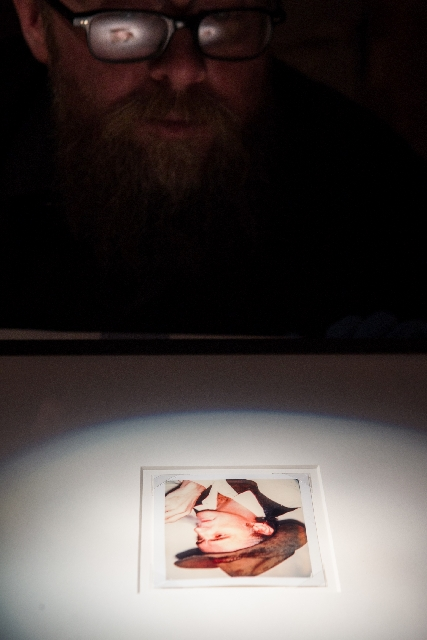 Bellagio art handler J.W. Caldwell examines a 1977 Polaroid portrait of Dennis Hopper by Andy Warhol.
