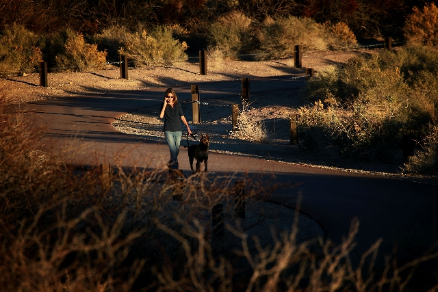 A woman walks a dog in Sunset Regional Park on Tuesday. Southern Nevada has experienced sunny, springlike weather for the past week, but that is expected to change starting today. The National Wea ...
