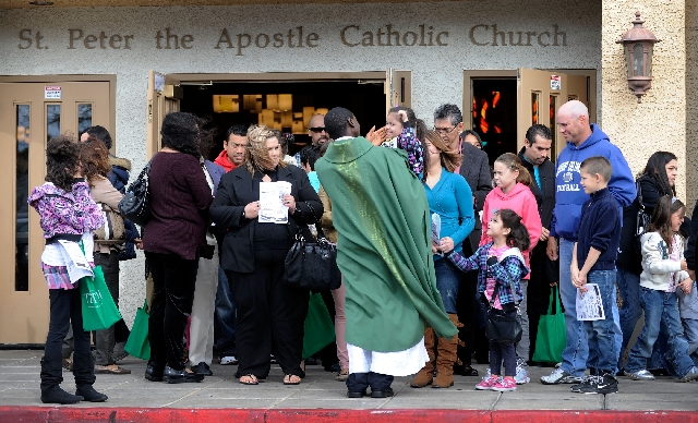 The Rev. Mugagga Lule greets parishioners after Sunday Mass at St. Peter the Apostle Roman Catholic Church. The parish's history has been intertwined with that of Henderson's for seven ...