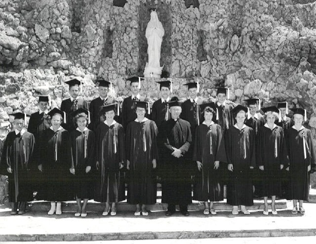 One of the graduating classes of the school operated by St. Peter the Apostle Roman Catholic Church poses in front of the church's signature, but now gone, grotto.