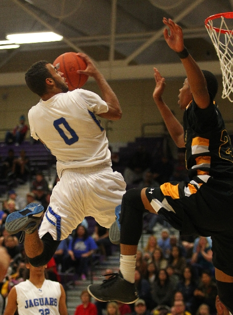Desert Pines guard Julian Jacobs goes to the basket against Clark forward Diontae Jones in the Division I-A Southern Region title game Saturday at Sunrise Mountain. Jacobs had 18 points, 10 assist ...