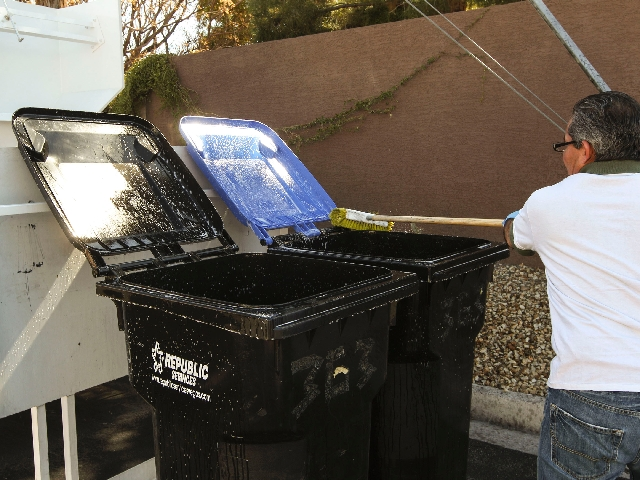 Juan Ochoa, who works for Queen of Cans, cleans trash bins Friday at a Las Vegas home.
