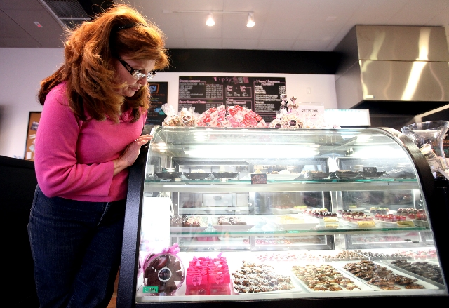 Kim Sostman, owner of the Tipsy Coffee House looks over the confections displayed in her shop. She started making desserts to please her co-workers before starting her own business in 2009. Many o ...