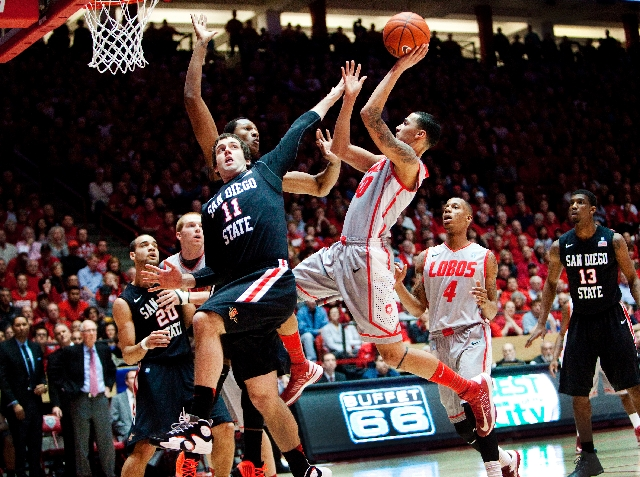 New Mexico's Kendall Williams shoots over San Diego State's James Rahon (11) and Skylar Spencer for two of his eight points in their Mountain West game in Albuquerque, N.M., on Wednesd ...