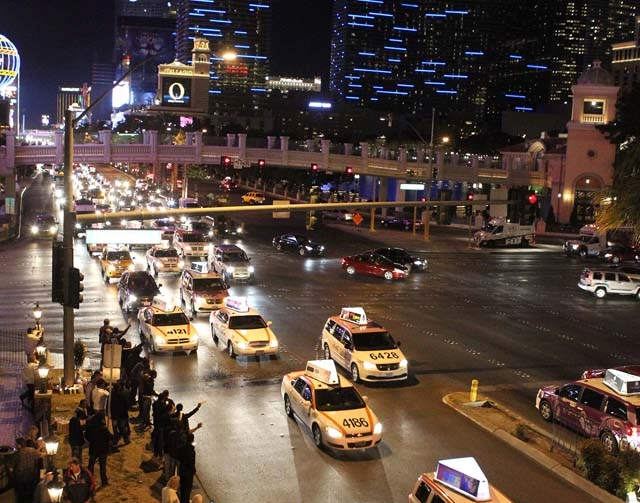 Hundreds of cabbies drive with their hazard lights on up Las Vegas Boulevard at Flamingo Road on Thursday as part of a vigil for cabdriver Michael Boldon, 62, whose cab exploded upon impact last w ...