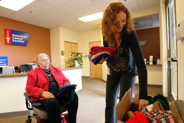 Erika Brassington-Stocks, quality of life manager at the American Cancer Society Great West Division, 6165 S. Rainbow Blvd., checks out hats donated Jan. 28 by cancer patient Jeanette Sprowl, left ...
