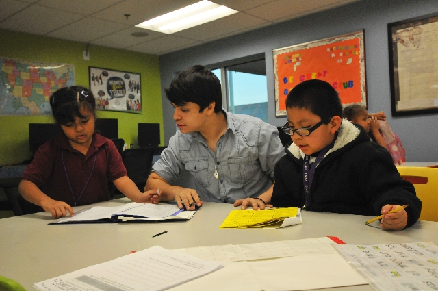 Boys & Girls Clubs of Las Vegas' Youth of the Year Jorge Corral, center, tutors 8-year-old Reyna Rodriguez, left, and 6-year-old Samuel Valles Feb. 4 at the James Clubhouse, 2530 E. Carey Av ...