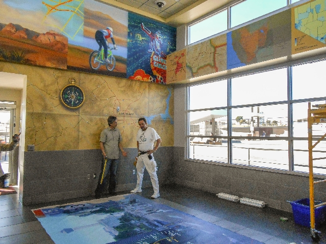 """Artist Mark Melnick, left, discusses the installation of his artwork with Candido """"Skip"""" Diaz Feb. 13 at the Westcliff Transit Center, 25 S. Durango Drive. The large panel on the floor ..."""