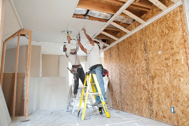Carpenters, from left, Jesus Garcia and Aron Ruiz screw in drywall on a foreclosed home for the Las Vegas Neighborhood Stabilization Program. The program helped 146 families purchase abandoned or  ...