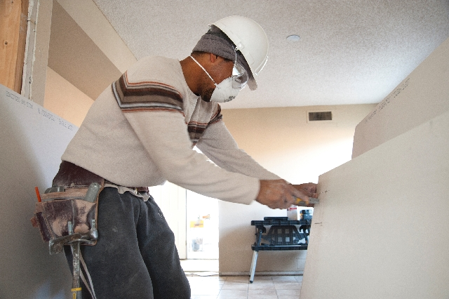 Carpenter Jesus Garcia cuts drywall Feb. 20 during an effort to fix a foreclosed home for the Las Vegas Neighborhood Stabilization Program.