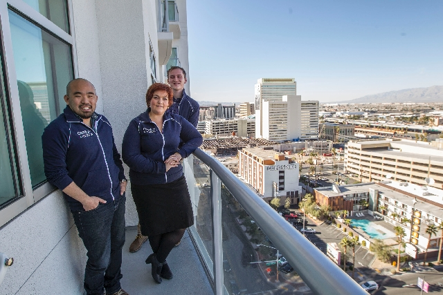From left, Code for America members Lou Huang, Lindsay Ballant and Ryan Closner stand on the balcony of their room Feb. 25 at The Ogden overlooking downtown Las Vegas.