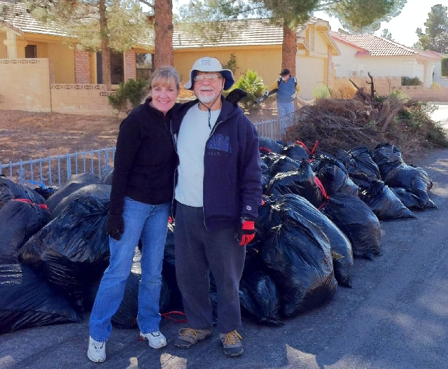 Rachelle Carter and Neighborhood Watch co-captain John Duggan stand in front of piles of garbage bags taken from a backyard cleanup. The community near Windmill Lane and Eastern Avenue rallied to  ...