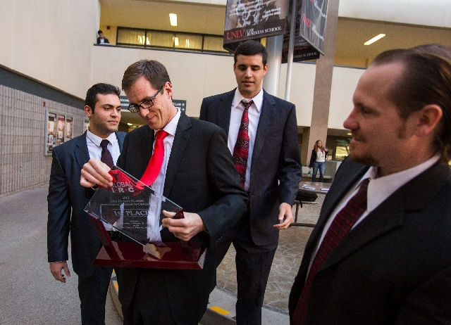 Jeffery Zemp, second from left, holds a trophy Thursday that he and Elias Shliyan, left, Sean Skinner, third from left, and Warren Stender, right, won last week during the CFA Institute Research C ...