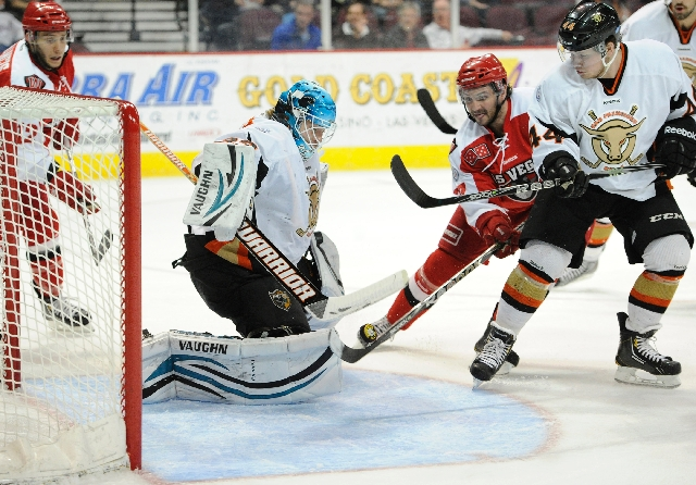 Wranglers right wing Sean Wiles, center, wards off Bulls defenseman Cody Carlson while shooting against goaltender Thomas Heemskerk in the first period Friday night at Orleans Arena. Wiles scored  ...