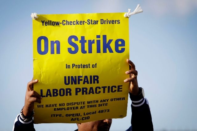 A cabby pickets outside Yellow-Checker-Star Transportation on Sunday during a drivers' strike. Yellow-Checker-Star Chief Operating Officer Bill Shanko said the company was able to fill about ...