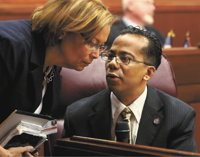 Nevada Assemblyman Steven Brooks, D-North Las Vegas, talks with his attache, Robin Carter, on the Assembly floor on Feb. 6. Brooks is facing several charges stemming from a domestic dispute with h ...