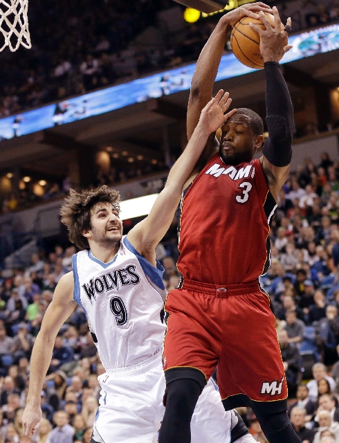 Miami guard Dwyane Wade hangs onto the ball while being fouled by the Minnesota Timberwolves' Ricky Rubio on Monday during the Heat's 15th straight victory, 97-81.