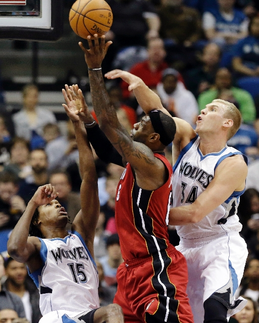 LeBron James of the Heat shoots while defended by Greg Stiemsma, right, and Mikael Gelabale of the Timberwolves on Monday night at Minneapolis. James scored 20 points in Miami's 97-81 victory.
