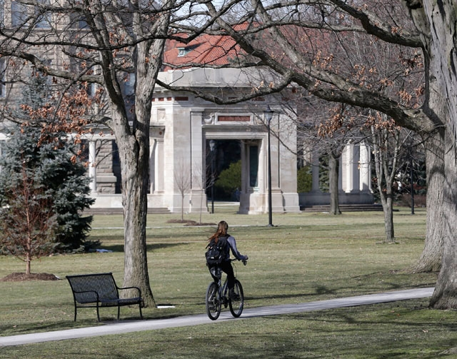A student rides a bicycle on the campus of Oberlin College on Tuesday in Oberlin, Ohio. Oberlin College  says it canceled classes after a report that a person wearing a hooded robe resembling Ku K ...