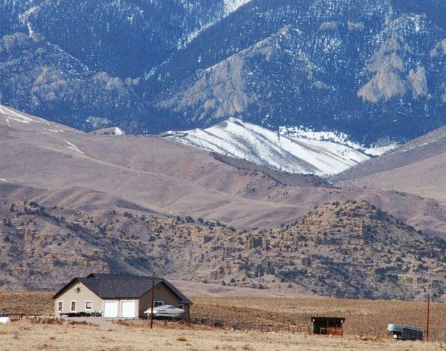 The Beartooth Mountains rise up behind a house in Clark, Wyo., on Tuesday where a woman and her parents where killed during an alleged vehicle theft. The violence has tested residents' perce ...