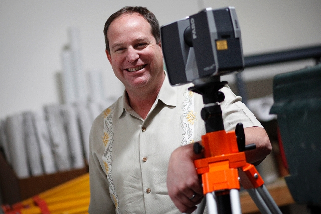 Kevin Wallace, president of Wallace Morris Surveying Inc., poses March 7 with a Faro Focus 3-D scanner at his company's office in Las Vegas.