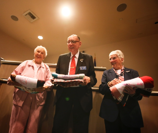World War II veterans, from left, Billie D'Entremont, 93, Richard Zimpfer, 90, and Evie Hallas, 90, hold quilts donated by Moms Love Quilts while being honored at Veterans Court graduation M ...