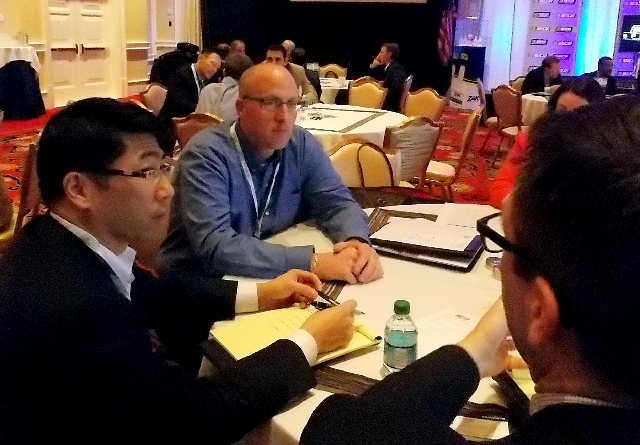 Justin Fantozzi, center, Goodyear marketing manager for global race tires, chats Friday with representatives of 3M at a NASCAR business-to-business session at Encore hotel-casino. NASCAR holds fou ...