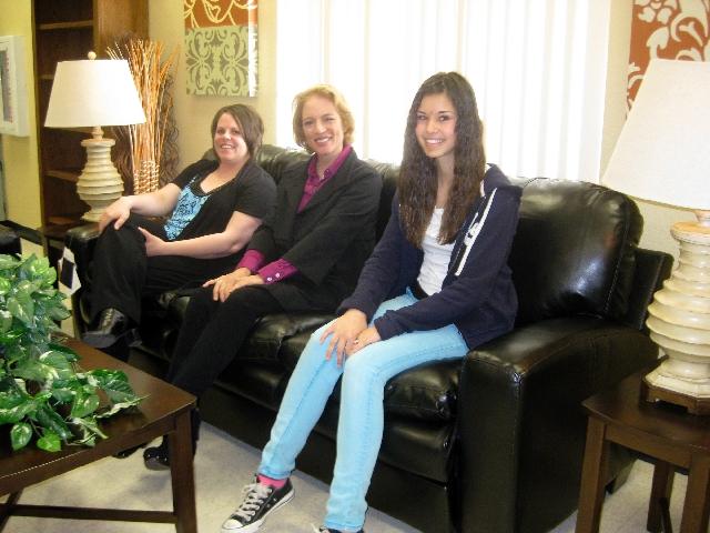 Seen sitting on a new sofa provided by Walker Furniture through the 13th annual Teacher Appreciation Day program are, from left, Canarelli Middle School teacher Shelly Rambur; Linda Alterwitz, dir ...