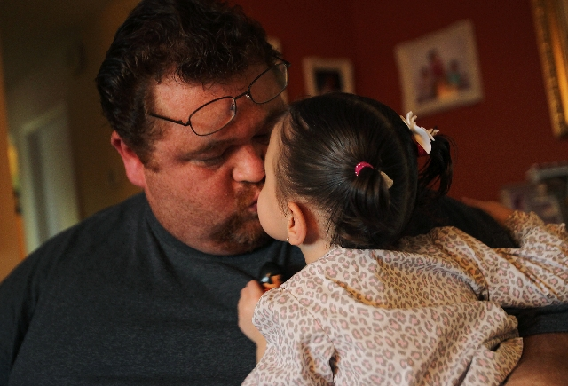 Omar Lazo showers daughter Sandra with affection. Easter Seals helps provide treatment for Lazo's daughters.