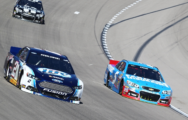 Kasey Kahne (5) dips down low in the Hendrick Motorsports Chevrolet to take the lead from Brad Keselowski in the Penske Racing Ford during the NASCAR Sprint Cup Series Kobalt Tools 400 on Sunday a ...