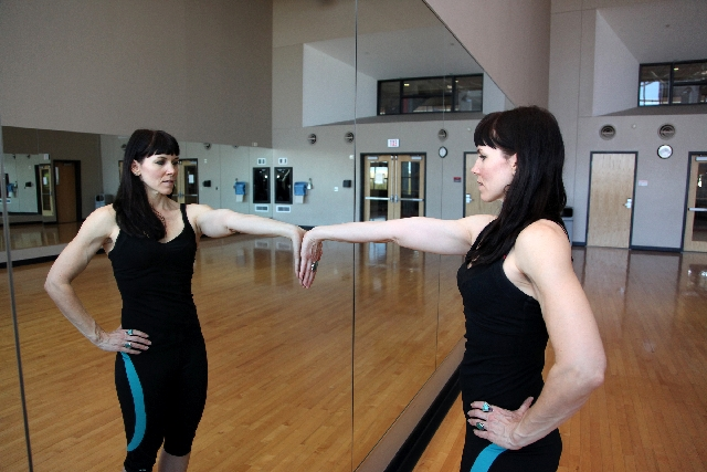 BICEPS STRETCH, START: Stand facing a wall. Place one palm on the wall at shoulder height with the fingers facing downward.