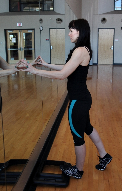 CALF STRETCH, START: Place the ball of the foot on a riser or step so the heel is on the floor. Have the leg and back straight and a hinge in the hip.