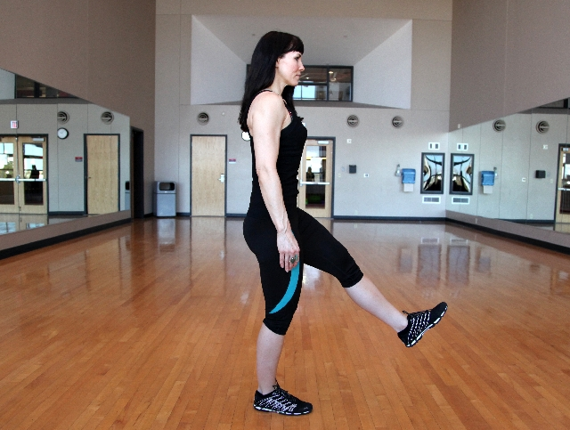 PISTOL SQUATS, START: Begin by standing with the feet hip width apart. Elevate one foot to the front while keeping the leg straight. Contract the core.