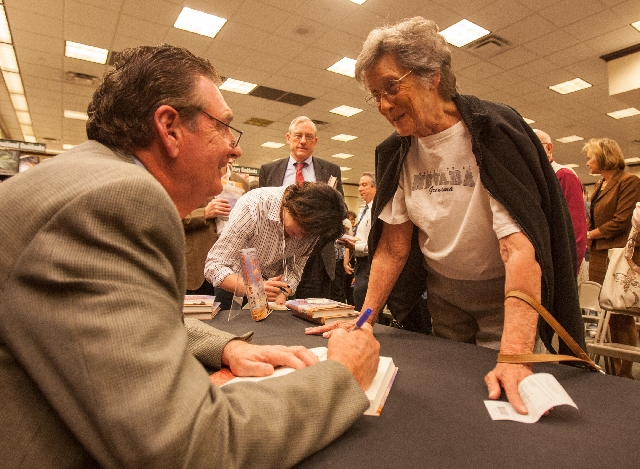 """Betty Brooks, right, talks with former Nevada Gov. Bob Miller after a reading as he signs his autobiography """"Son of a Gambling Man"""" for her at Barnes & Noble. Brooks, who worked at the ..."""