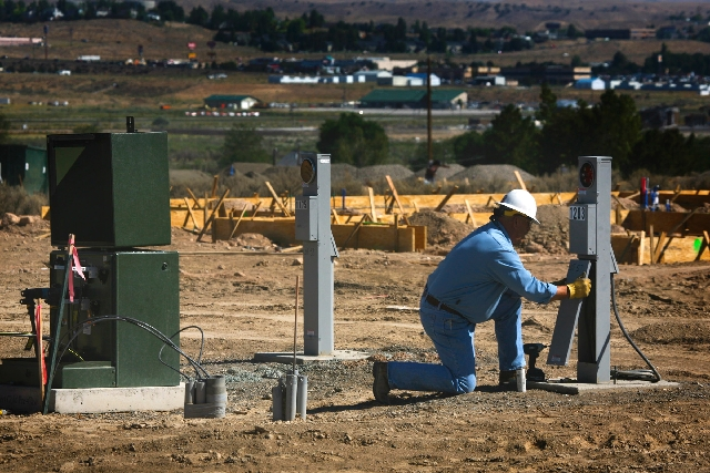 NV Energy worker Paul Otten hooks up power in August to Artisan, a single-family home community in Elko, which gained 1,787 new people in 2012.