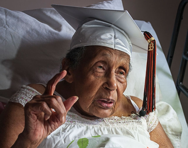 With friends and family watching, Reba Williams, 106, receives her high school diploma from Mount Vernon Schools Superintendent Steve Short (not shown) at her home in Columbus, Ohio, on Wednesday, ...