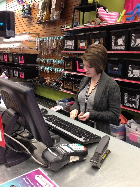 Tory Sherman works the cash register at Plato's Closet at 5643 Centennial Center Blvd.