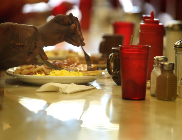 A Tiffany's Cafe diner eats breakfast Thursday. Owners of the 65-year-old 24-hour diner, tucked inside the White Cross Drug building, are hoping the full-size White Cross Market will boost b ...