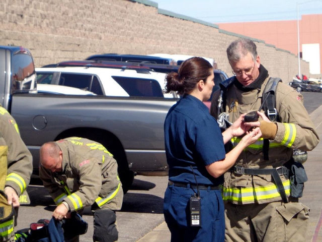 Henderson firefighter Anna Winterspeen helps Henderson Mayor Andy Hafen put on firefighter gear during a training simulation with city officials and community partners at the Fire Training Center  ...