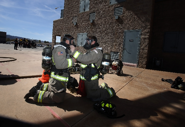 Henderson firefighter Kenny Ramirez, right, assists View reporter Michael Lyle in putting on breathing apparatus during a training simulation with city officials and community partners at the Fire ...