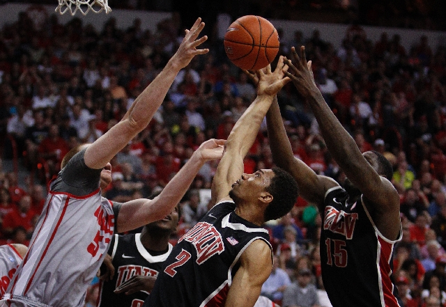 Khem Birch of UNLV, center, grabs a rebound against New Mexico during the Mountain West tournament championship at the Thomas & Mack Center on Saturday.