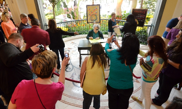 """Dale Chihuly autographs copies of his new book, """"Chihuly Silvered,"""" on Saturday at Bellagio, where his glass sculpture """"Fiori di Como"""" hangs in the lobby."""