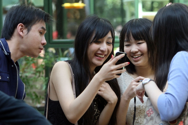 University of Southern California students from Taiwan look at photos of themselves amid the flowers at the Conservatory & Botanical Gardens in the Bellagio hotel-casino on Monday. The students, f ...