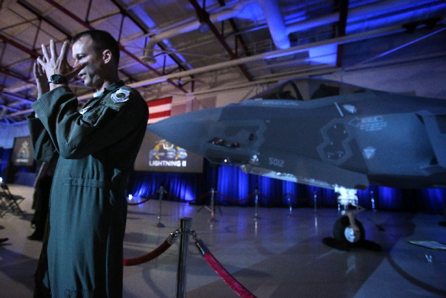 """Air Force Maj. Joe """"Five-O"""" Sholtz talks about the helmet he uses when flying the F-35 Lightning II Joint Strike Fighter during Tuesday's arrival ceremony for the plane at Nellis ..."""