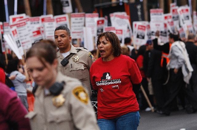 In an act of civil disobedience, Geoconda Arguello-Kline, middle, Secretary-Treasurer of the Culinary Workers Local 226, gets arrested on the Las Vegas Strip in front of the Cosmopolitan Hotel dur ...