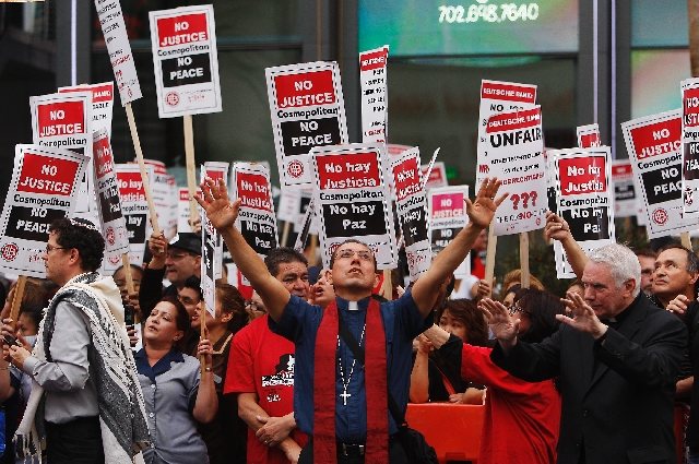 The Rev. Hilario Cisneros prays Wednesday as members of the Culinary union block traffic on the Strip in front of the Cosmopolitan.